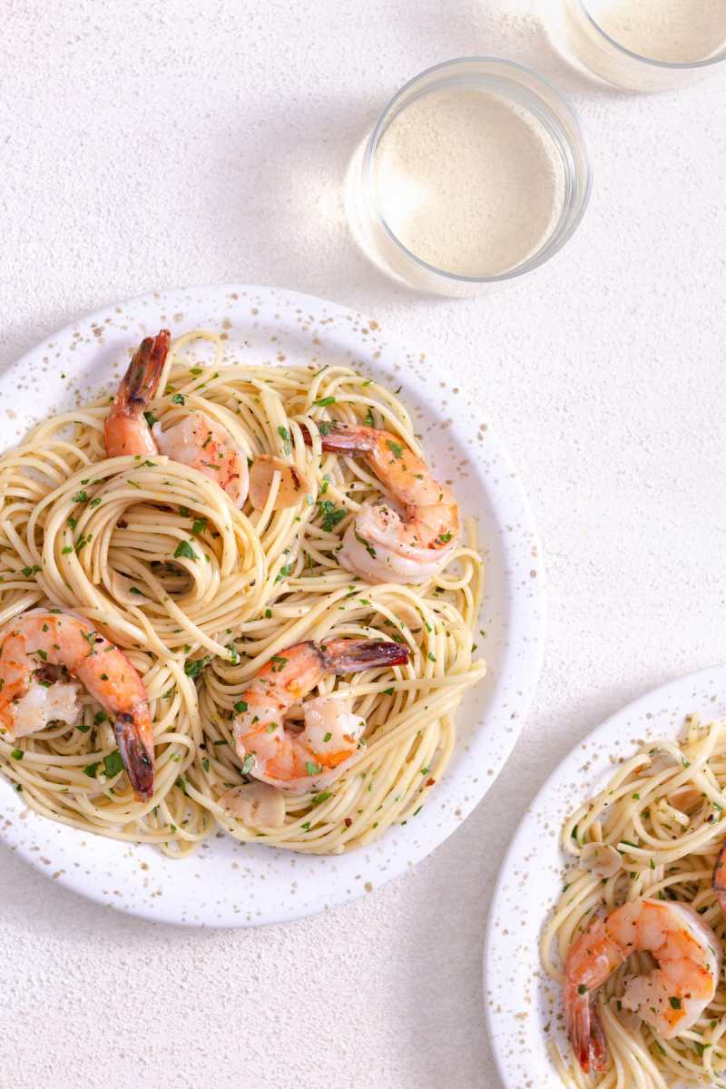 Overhead view of a plate of shrimp scampi pasta surrounded by a wine glass on a white plaster surface.