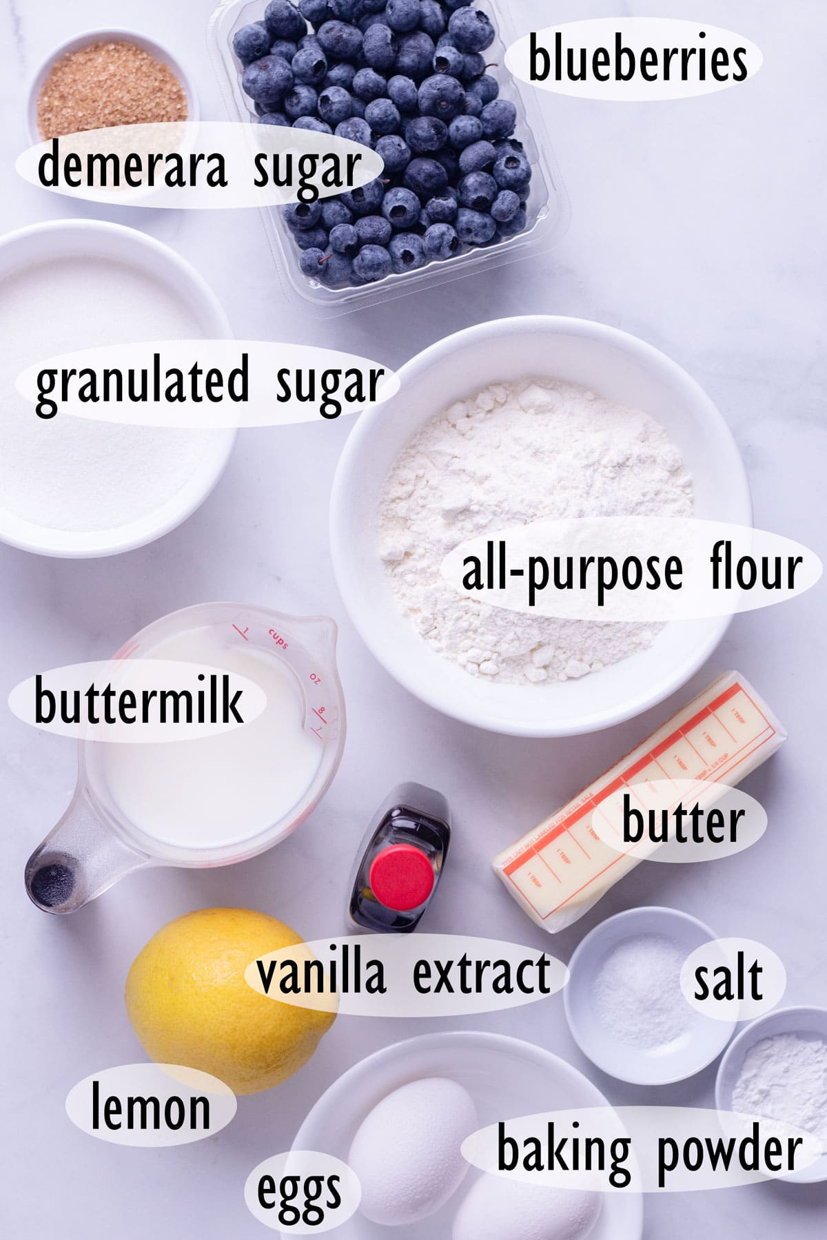 Overhead view of ingredients for blueberry muffins, including flour, buttermilk, butter, sugar and eggs.