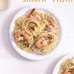 Overhead view of a plate of lemon garlic shrimp pasta next to wine glasses on a plaster surface.