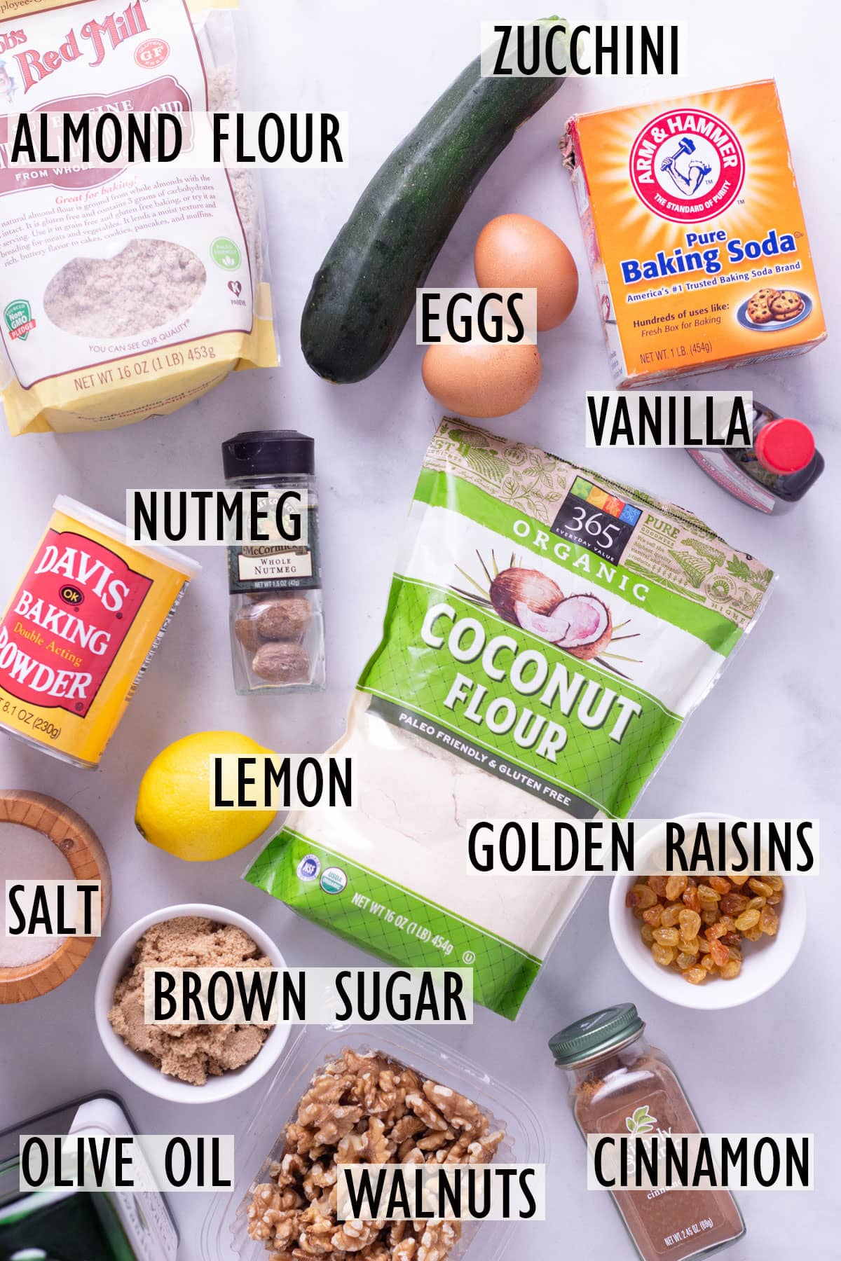Individual ingredients needed for zucchini bread, including almond flour, coconut flour, zucchini, eggs, brown sugar, walnuts and raisins.