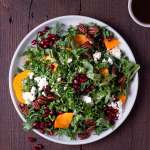 Overhead shot of a plate of kale salad with pomegranates, persimmons, pecans and feta cheese.