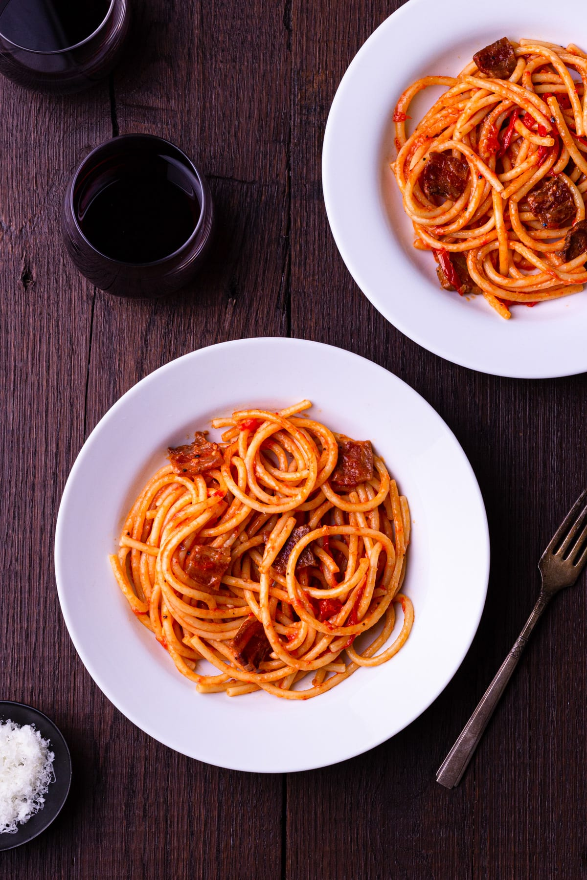 Overhead view of two bowls of Bucatini All'Amatriciana on a dark wood surface surrounded by glasses of red wine a fork.