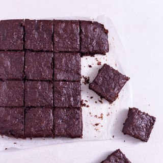 Avocado Brownies cut into squares on a cream surface near a glass of milk.