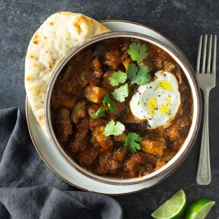 Overhead view of a bowl of Indian inspired lamb curry surrounded by yogurt, lime wedges and naan on a dark grey surface.