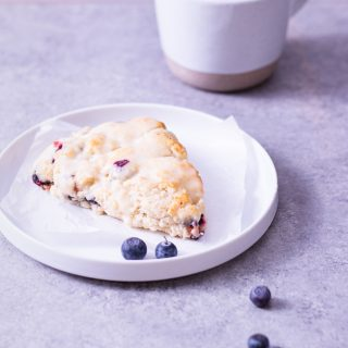 Straight on shot of a blueberry scone on a white plate next to a cup of coffee on a light grey surface.