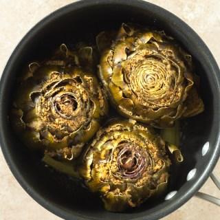 Overhead image of stuffed artichokes in pot on beige textured surface