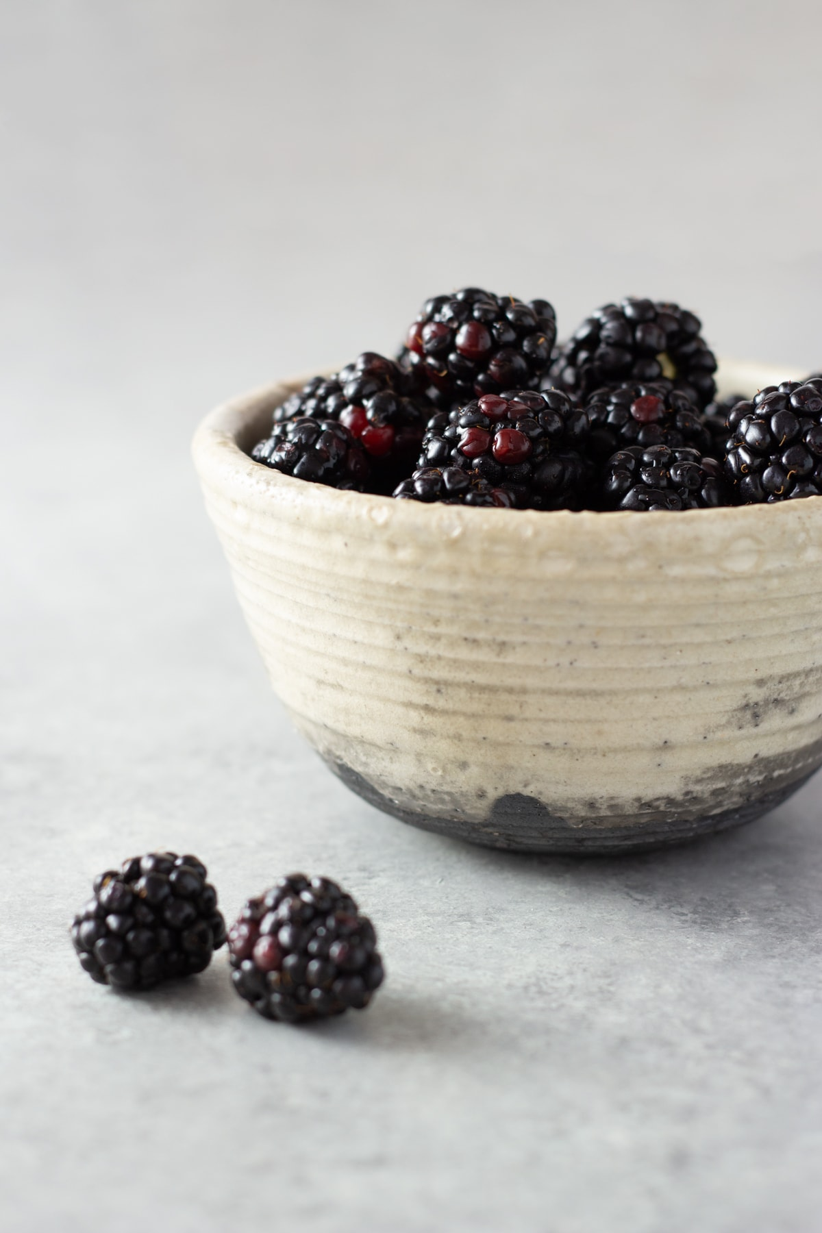 Straight on shot of a rustic bowl filled with fresh blackberries on a light grey surface.