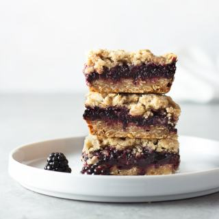 Straight on view of a stack of 3 Blackberry Oatmeal Crumb Bars on a white plate with a light background.