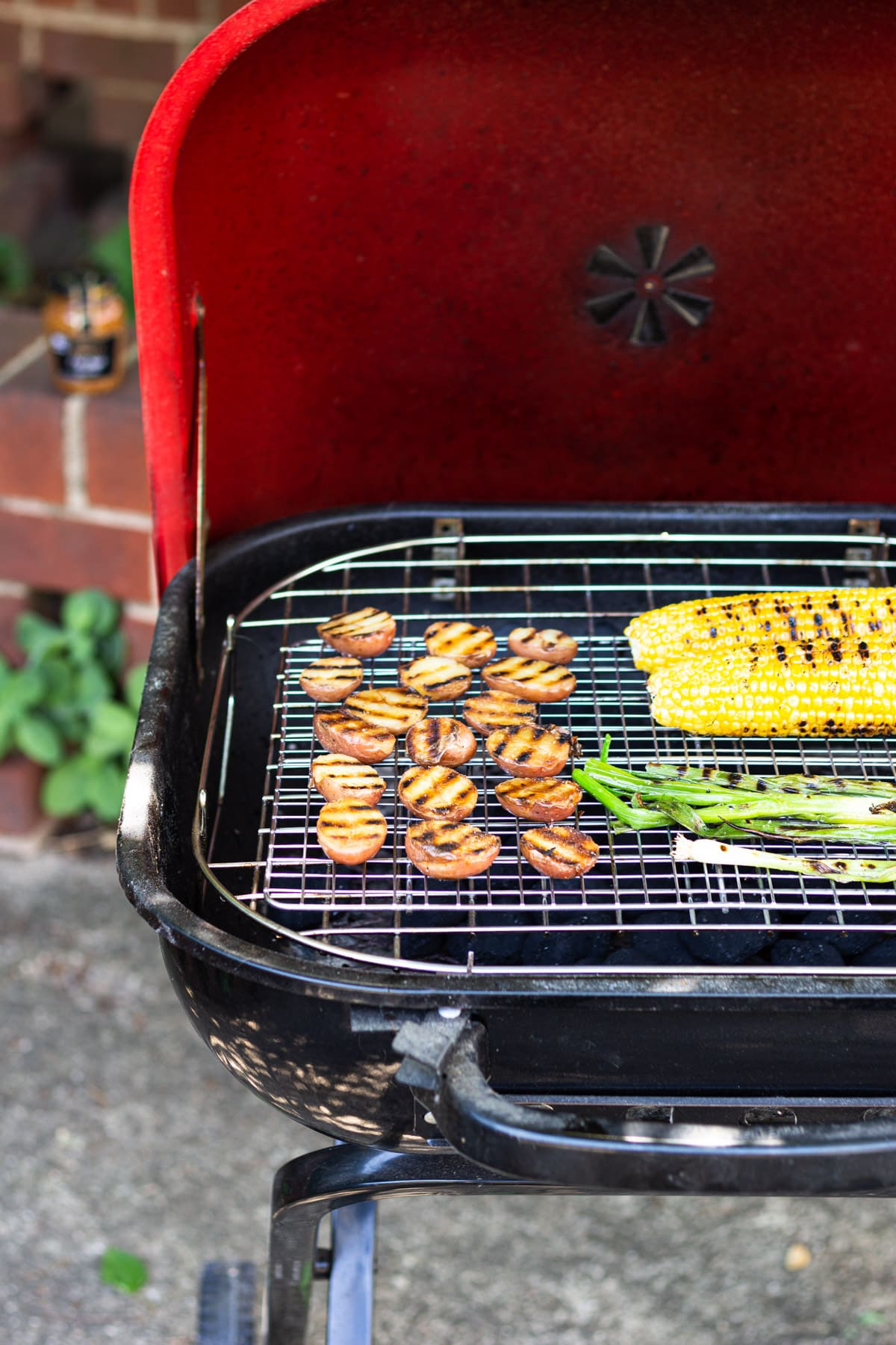 Red potatoes, corn on the cob and scallions on an outdoor grill.