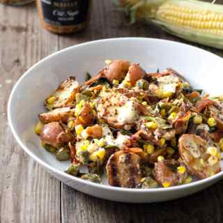 A bowl of Grilled Potato Salad with corn, bacon, and scallions on a wood surface.