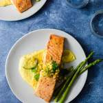 Miso Butter Salmon over Corn Puree next to asparagus on a light grey plate with a vibrant blue background.