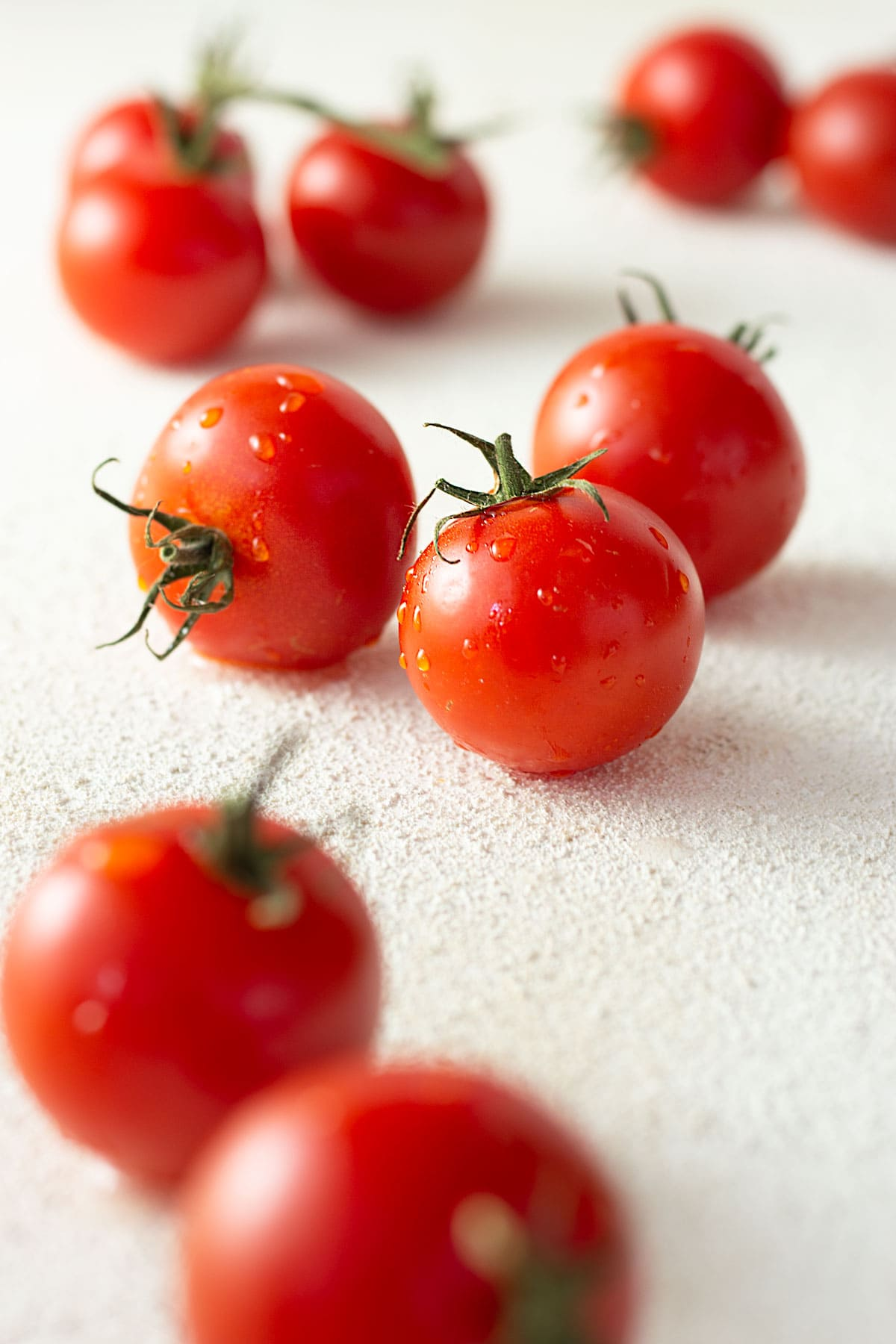 Straight on close up view of a group of compari tomatoes with water droplets on them.