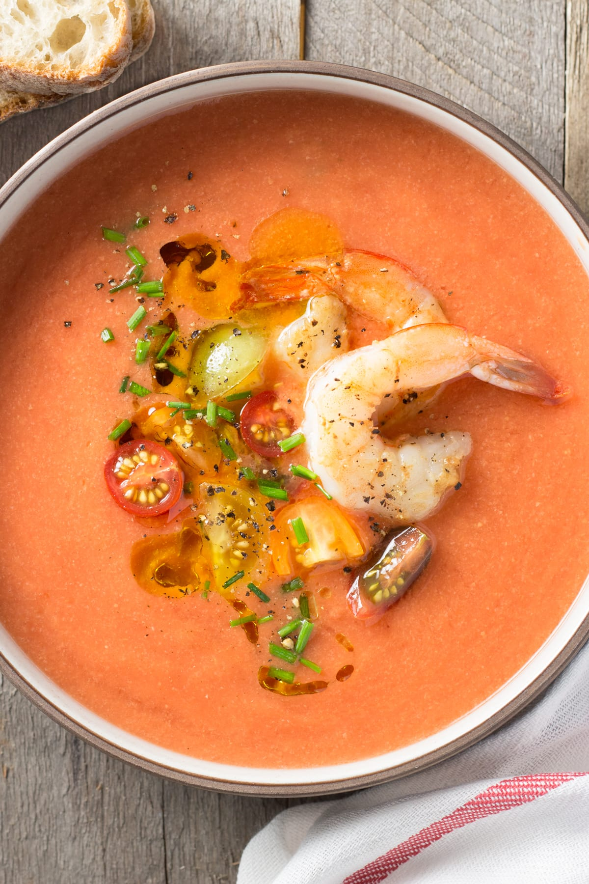 Overhead view of a bowl of tomato gazpacho topped with shrimp, sliced tomatoes and chives on a wood surface.