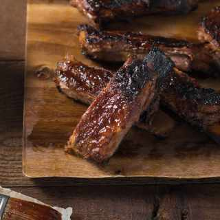 Closeup of a group of Korean BBQ Pork Ribs on a wood cutting board.