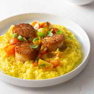 Angled view of a plate of Seared Scallops with Fresh Corn Polenta and Tomato Salad.