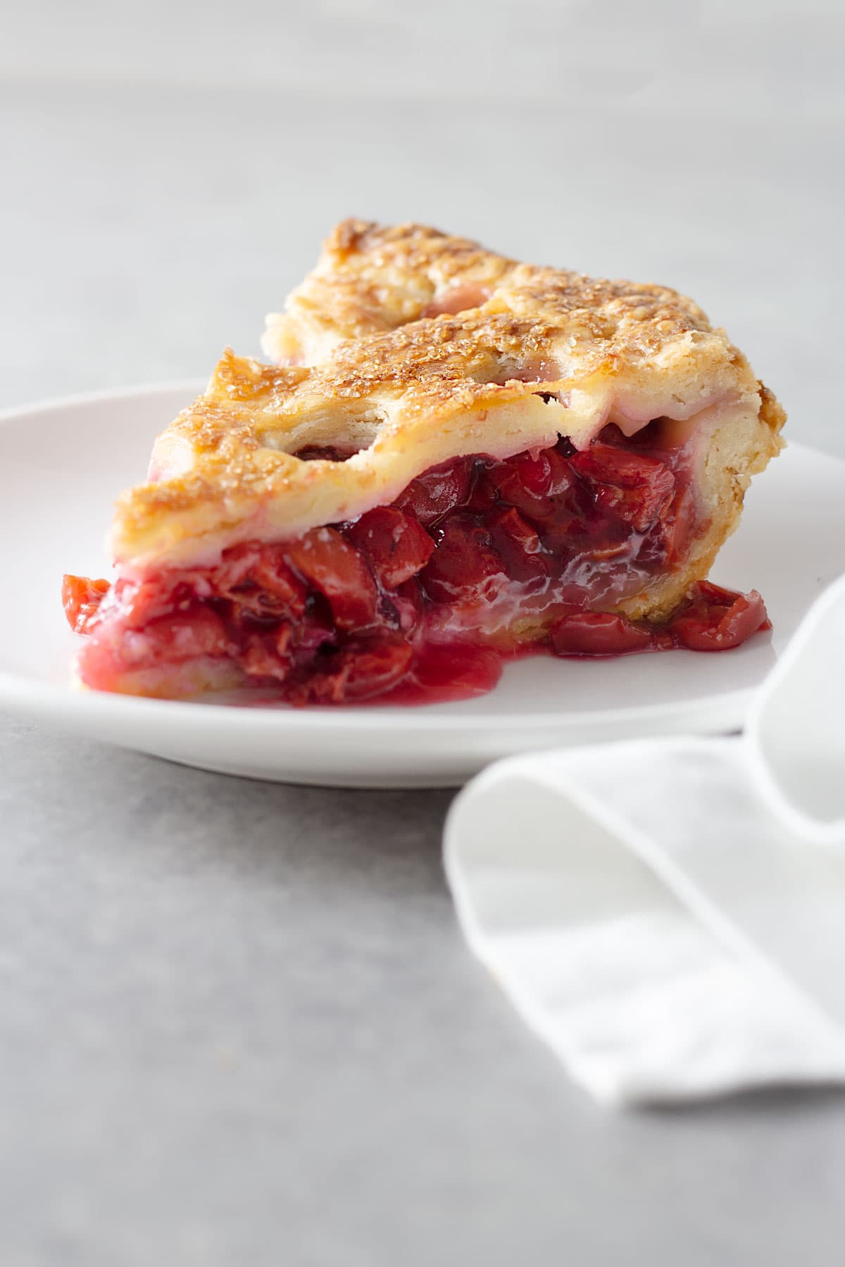 Closeup of a slice of Sour Cherry Pie on a white plate on a light grey surface.