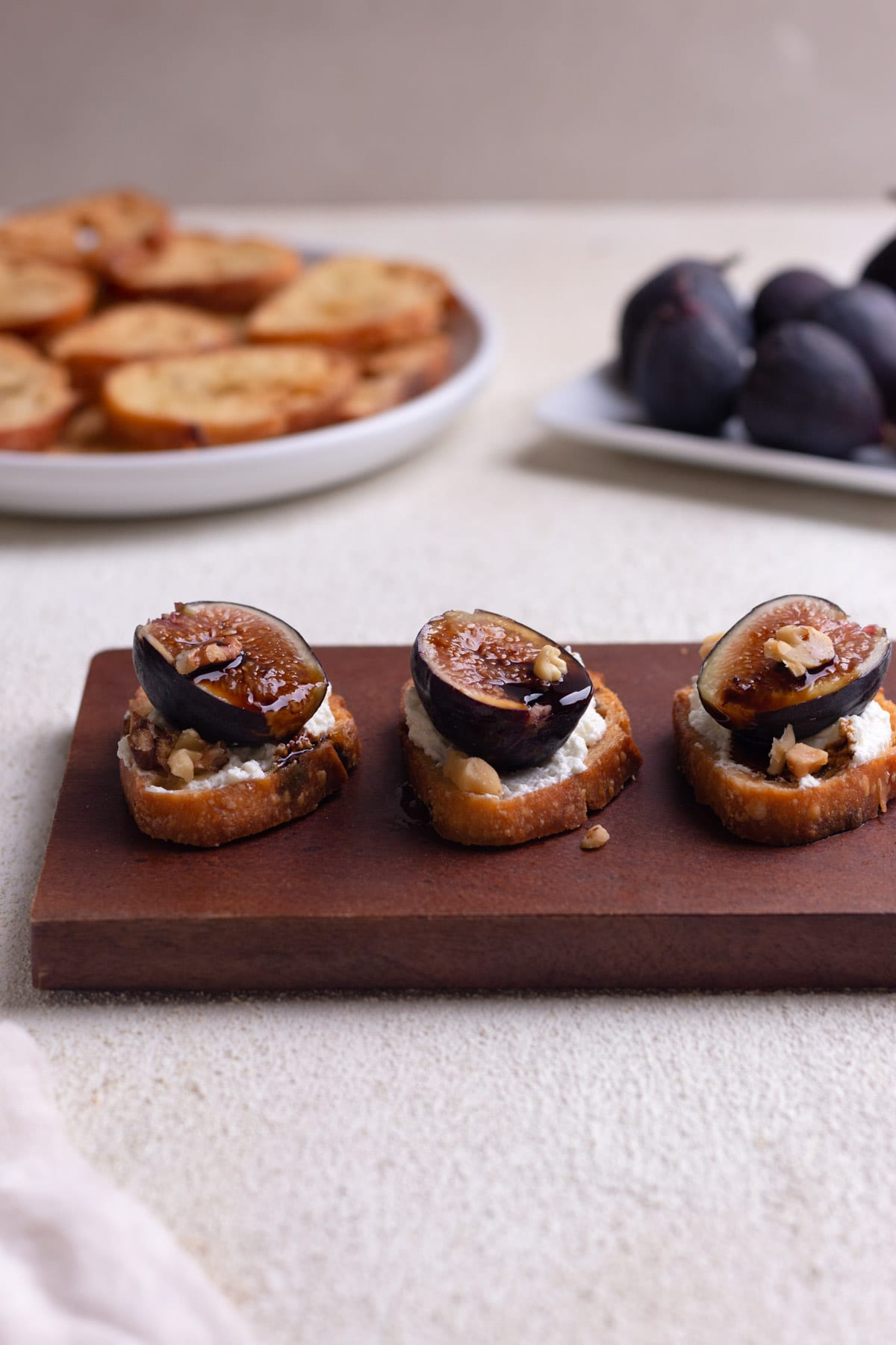 Fig and goat cheese crostini with balsamic on a wood cutting board on a cream, textured surface.