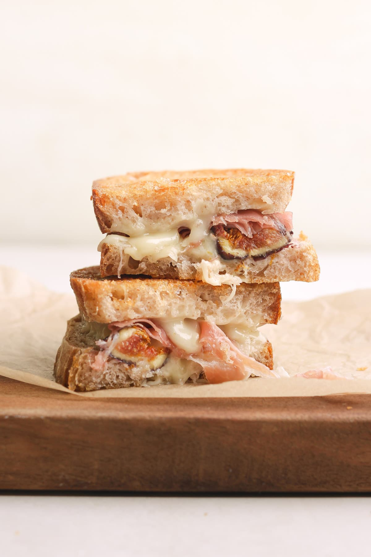 Straight on view of a Prosciutto Grilled Cheese with Figs and taleggio sliced in half and stack on top of itself on a wood cutting board.