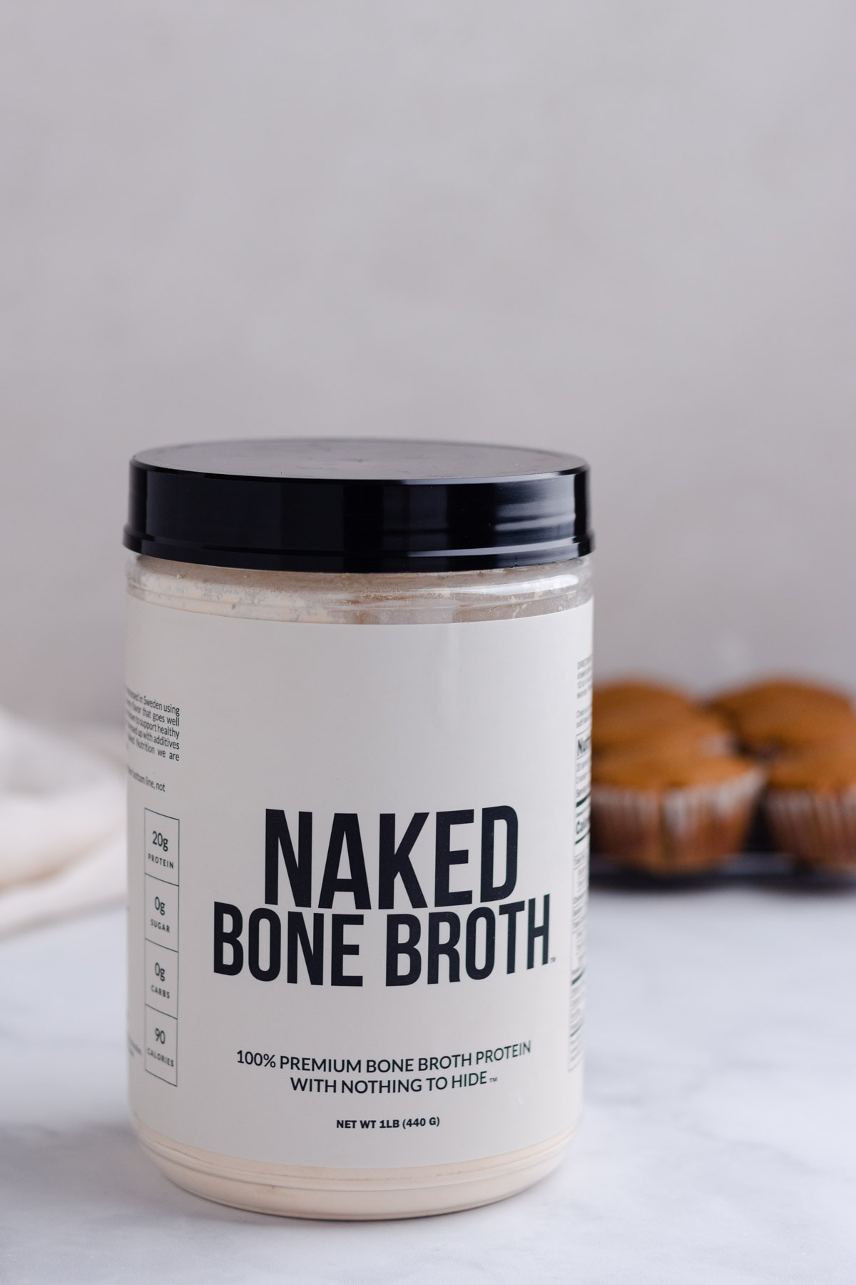 A close up of Naked Bone Broth protein powder with muffins in the background.