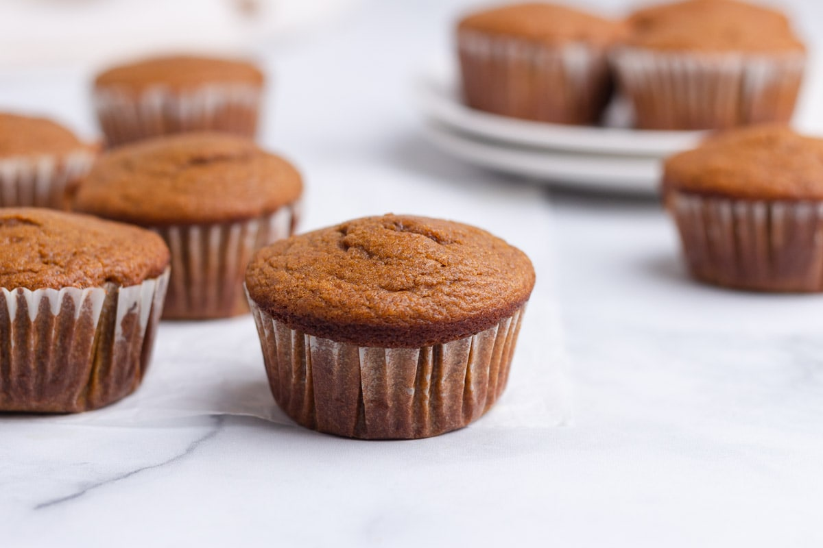 A group of pumpkin muffins on a marble surface.