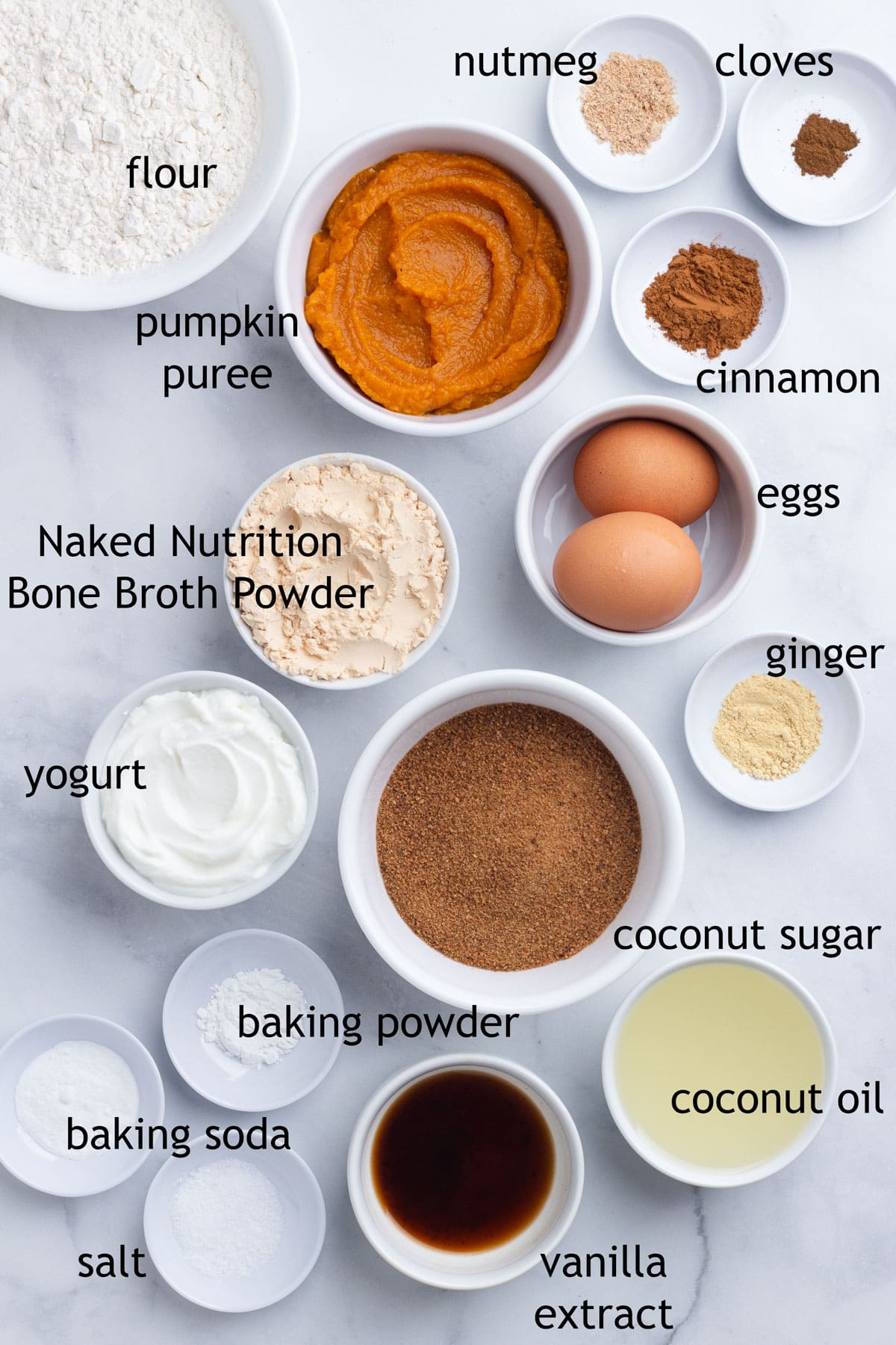 Ingredients for muffins including flour, pumpkin puree, spices, protein powder, eggs, coconut sugar, coconut oil and yogurt.