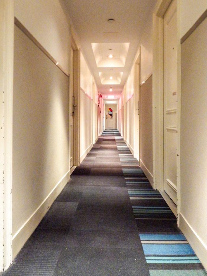 hotel hallway with beige walls and dark carpet