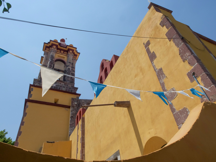 2 days in San Miguel de Allende travel tips | yellow church with flags #sanmigueldeallende #mexico #traveltips #timebudgettravel #sanmiguel #church