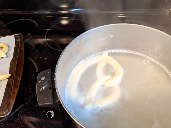 soft pretzel dough floating in a baking soda bath