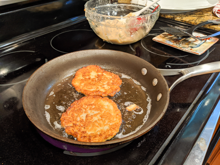 frying potato pancakes in oil on a stovetop