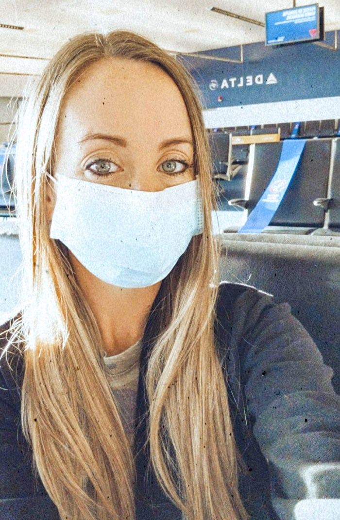 Blonde woman in a mask at the airport traveling during the pandemic