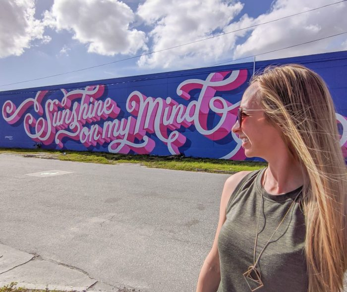 Sunshine On My Mind mural in St. Petersburg, Florida and me standing in front of it