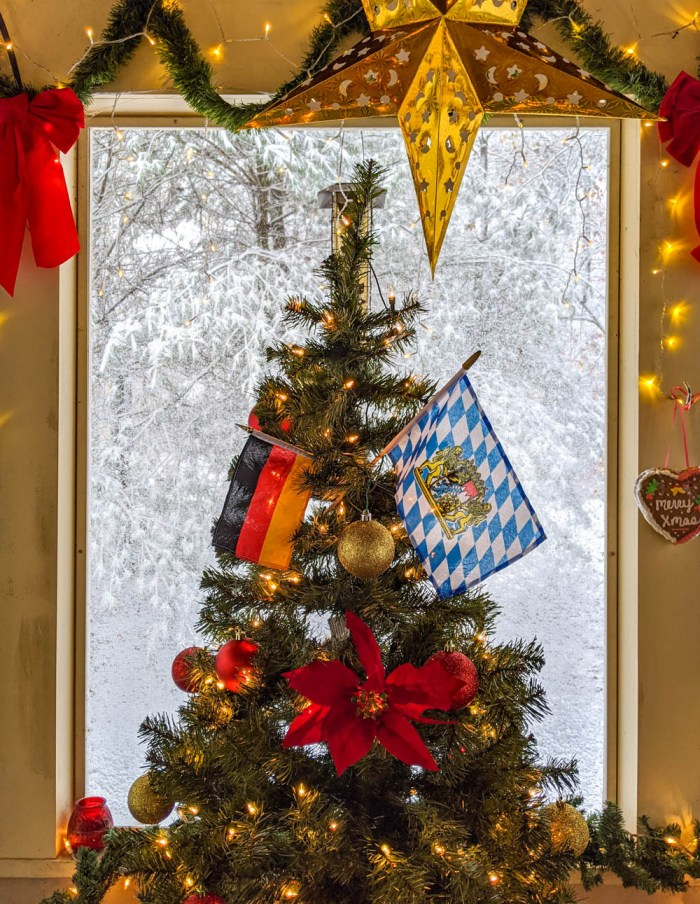 Christmas tree decorated with German flags surrounded by snow and stars
