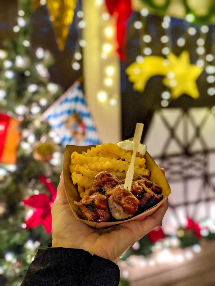 german currywurst and fries in front of bright christmas decorations