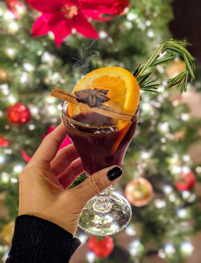 glass of hot spiced wine garnished with an orange and cinnamon stick in front of a christmas tree