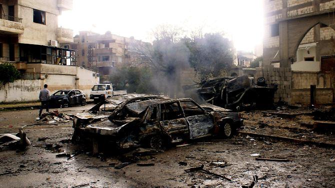 Ausgebombte Autos und Häuser in Homs.