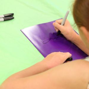 Young girl writes her name on a folder with a sharpie.