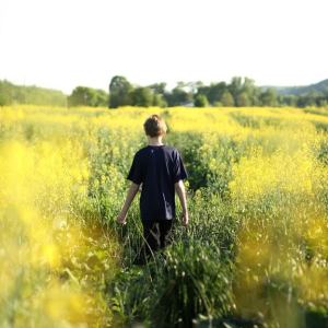 Boy walking through grass
