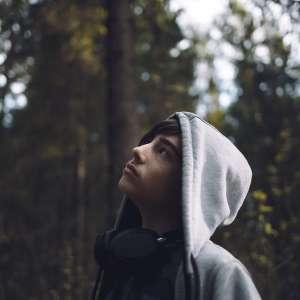 Teenage boy looking up at treetops