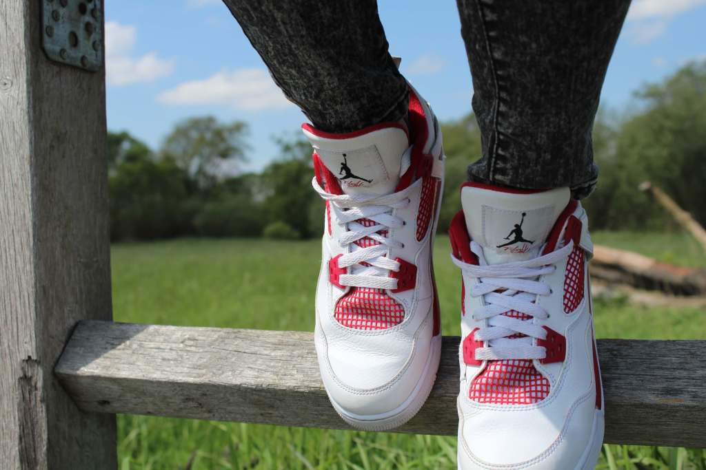 White and red sneakers on wooden fence