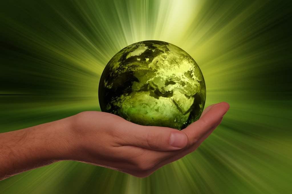 das Bild zeigt eine grüne Weltkugel in einer geöffneten Hand und symbolisiert so das System Nachhaltigkeit