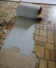 This older style of vinyl flooring has been peeled back to reveal a layer of asbestos beneath, similar to older linoleum that was also manufactured before 1969.