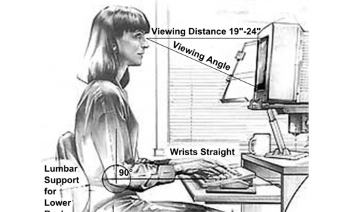 Una trabajadora usando un ordenador, mostrando las distancias apropiadas para una buena ergonomía.