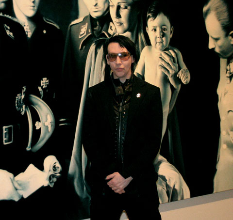 Manson posing at the right hand of the Messiah, Baby Hitler, Gottfried Helnwein, with baby Jesus or Adolf Hitler being admired by Nazi SS men.