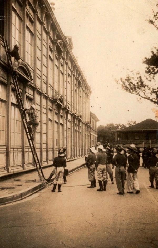 """1954. Práctica de rescate de bomberos voluntarios de la estación del barrio Luján en el """"Edificio Metálico"""" (centro de San José). El INS se levantó en el fondo."""