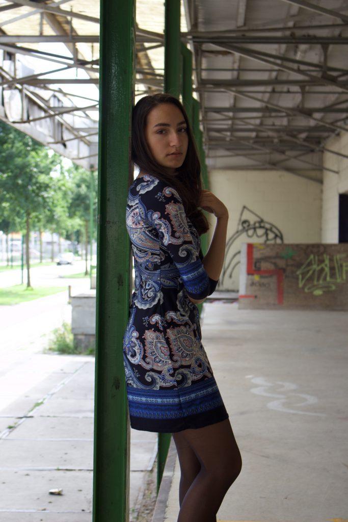 Nadeche Jocelyn in Primark jurkje met lakschoenen op een industrieterrein.