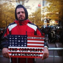 "Protestor at Zuccotti Park in New York City holding a sign that reads, ""End Corporate Personhood."""