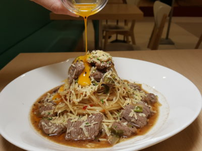 Food Lovers Only At IMM Serving Korean Fusion Items - Korean Bulgogi Pasta with egg pouring shot