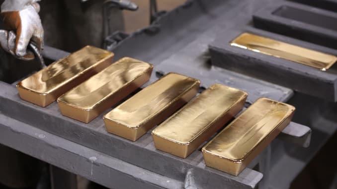 Gold inches up on weaker dollar, stimulus hopes