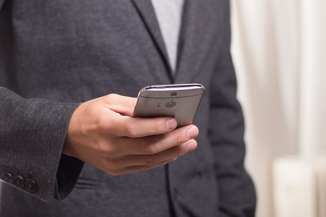 A man in suit operating a smartphone