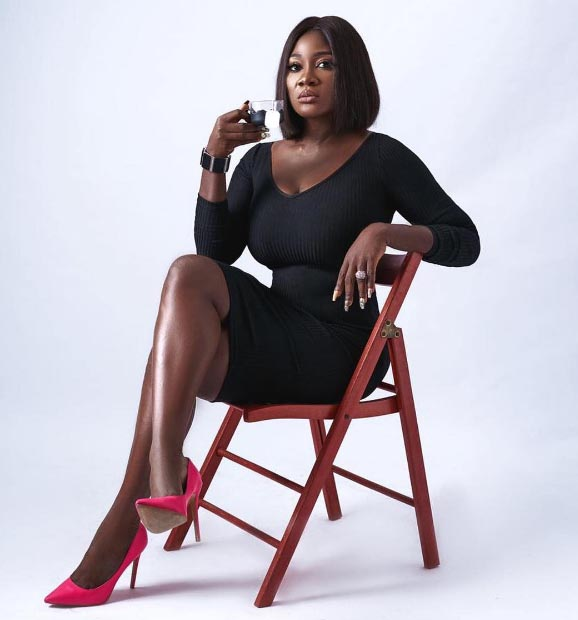 Mercy Johnson rocking a black gown and a red shoe